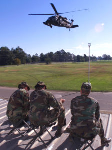 A Blackhawk helicopter flies over air traffic controllers from the Air Support Operations Squadron, North Carolina Air National Guard, and  North Carolina Army National Guard, in Tarboro, N.C., Friday, Sept. 24, 1999. (Photo by SSG Bob Jordan, 382nd MPAD, NCANG) Image courtesy US Army.