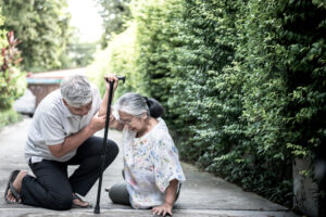 Elderly couple, husband helps wife who has fallen on the sidewalk