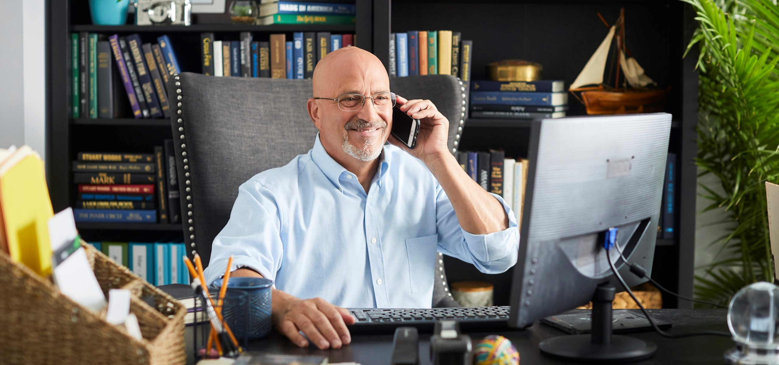 Man in his 60s smiling takes a phone call in front of his computer monitor
