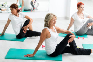 women doing yoga on teal yoga mats