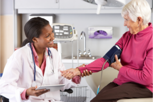 Doctor Taking Senior Female Patient's Blood Pressure