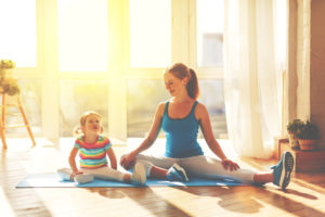 Mother and daughter on yoga mat