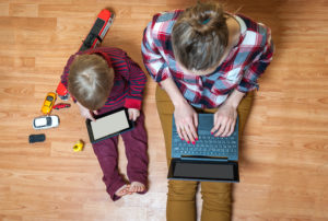 Mom and son work on tablets