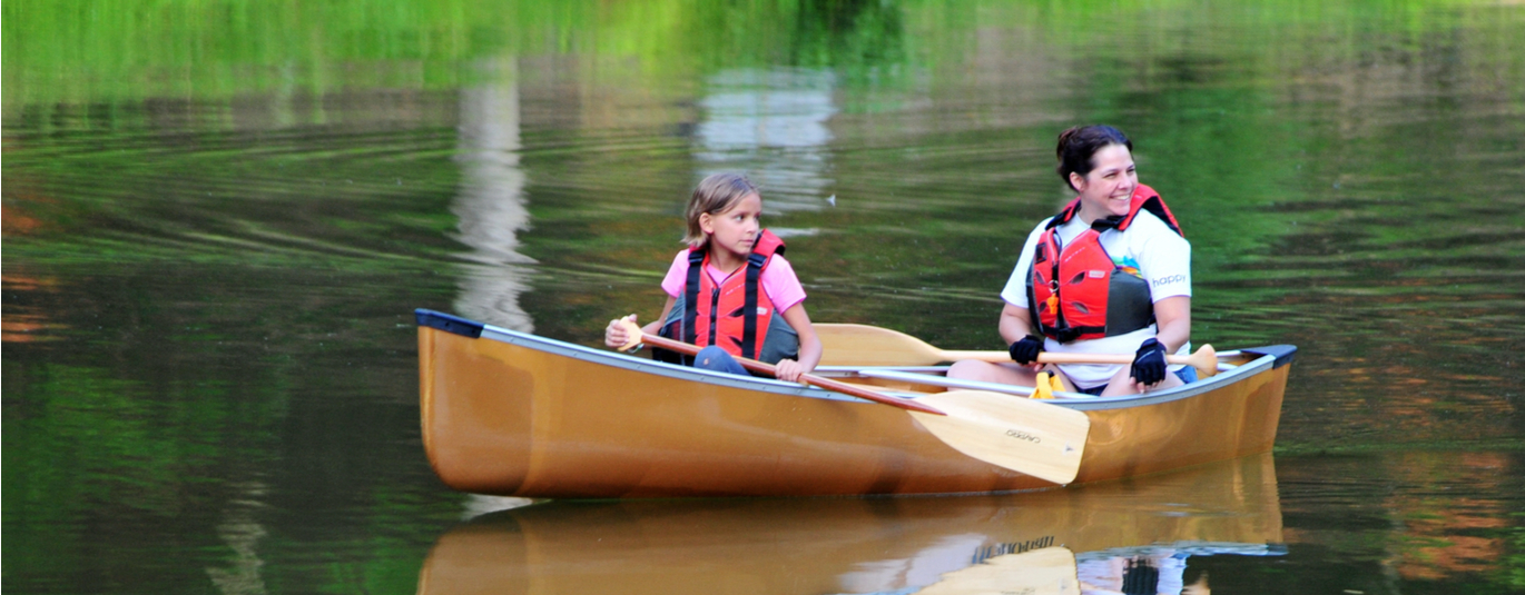 Mother and daughter canoe on a lake