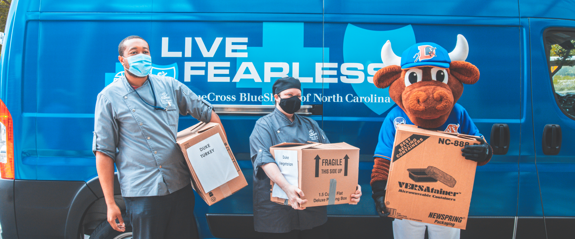Durham Bulls mascot and volunteers carry boxes full of meals