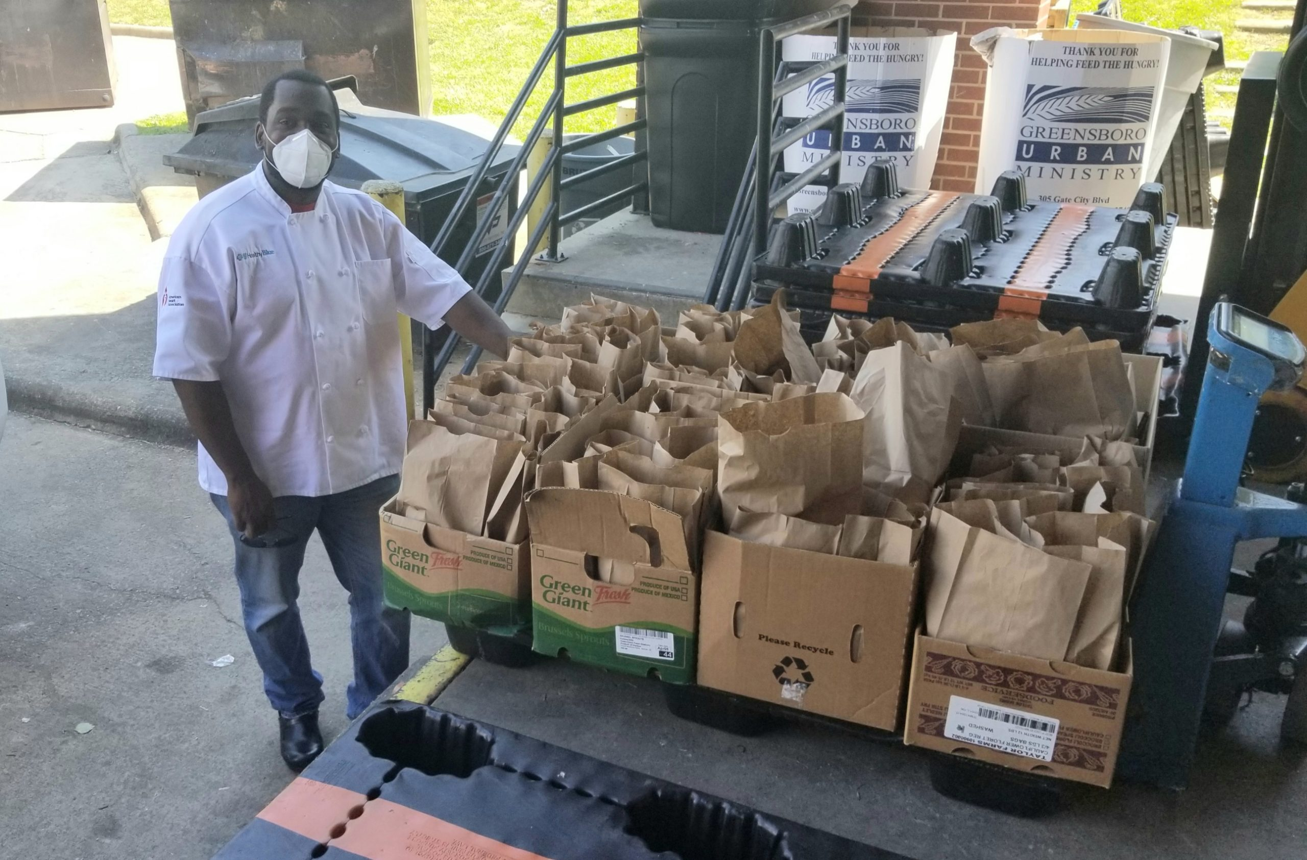 N'Gai stands next to a dozen brown bags full of meals