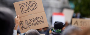 "Protest sign reads ""end racism"""