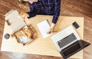 woman eating pizza at desk
