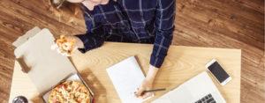 woman eats pizza at desk
