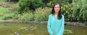 Preeti smiling in front of a pond and garden
