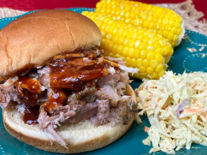 Pulled pork sandwich with corn on the cob and sauerkraut
