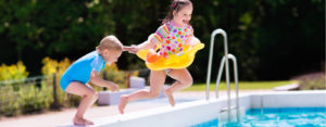Kids jumping in backyard pool