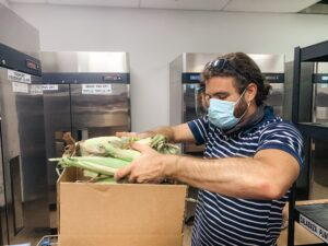 Man packs ears of corn into boxes to feed the hungry