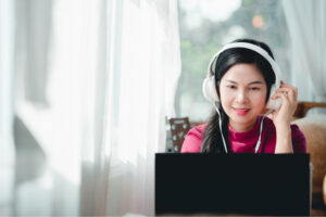 Woman with headphones smiles at laptop camera
