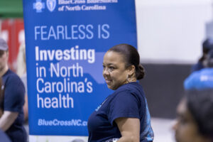"Blue Cross volunteer in front of a sign that reads ""investing in North Carolina's health"""