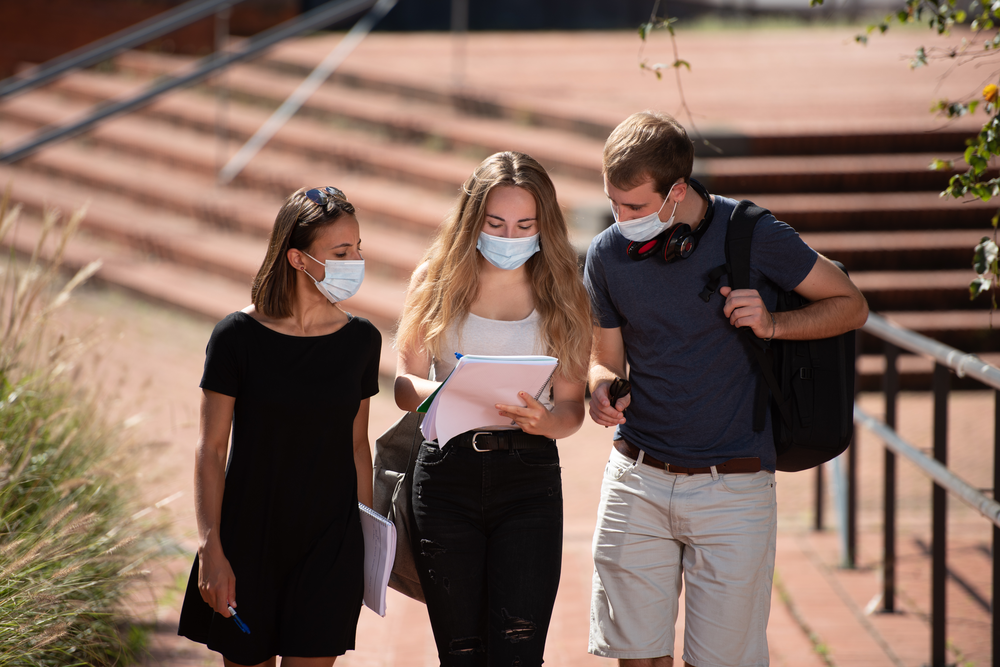 College students in masks socialize
