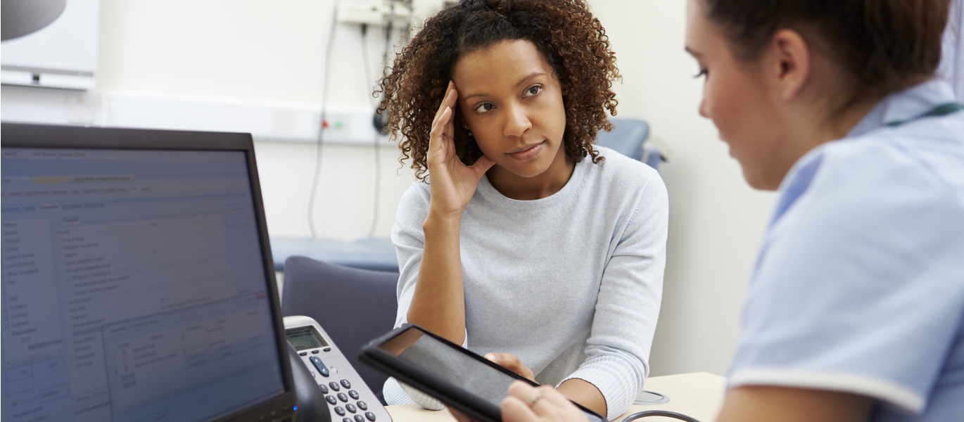Patient and doctor sit in front of computer monitor to discuss symptoms