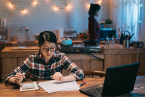 Young woman studies bill at kitchen table