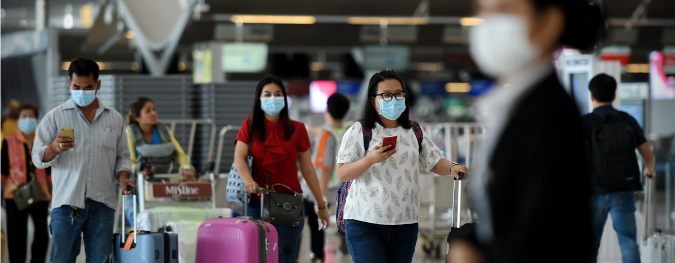 Travelers wearing masks in airport