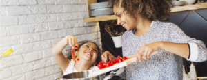 Woman and her young daughter cook bell peppers over the stove