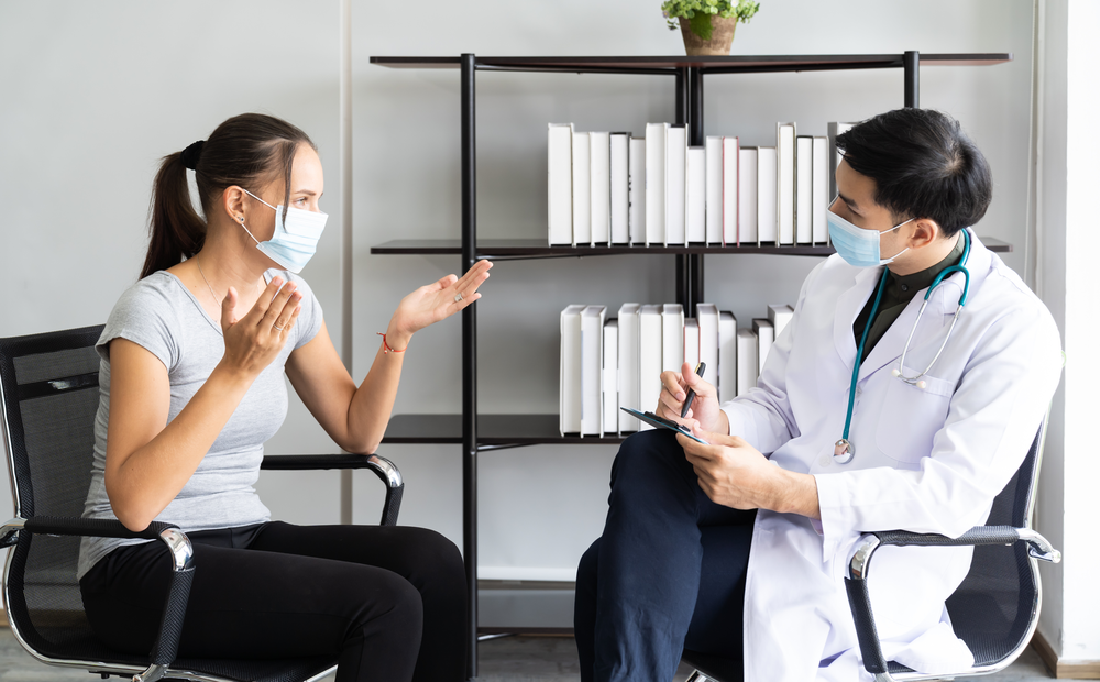 Doctor talks with patient, both wearing masks