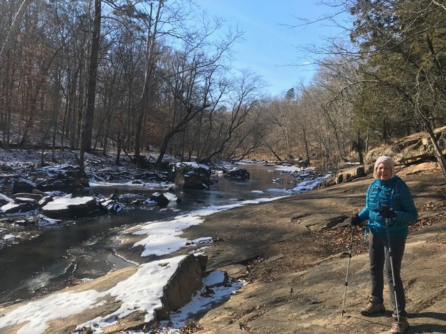Woman hikes by icy river in the winter