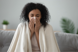 Woman with the flu under a blanket