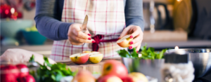 close-up of woman's hands cutting up apples in the kitchen