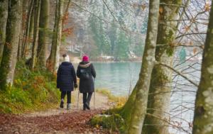 Backs of two women in winter gear hiking beside a lake