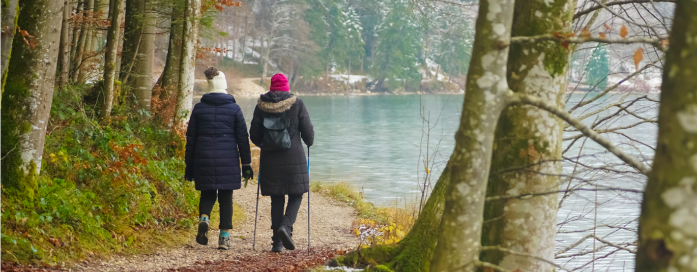Backs of two women in winter gear hiking beside a lake