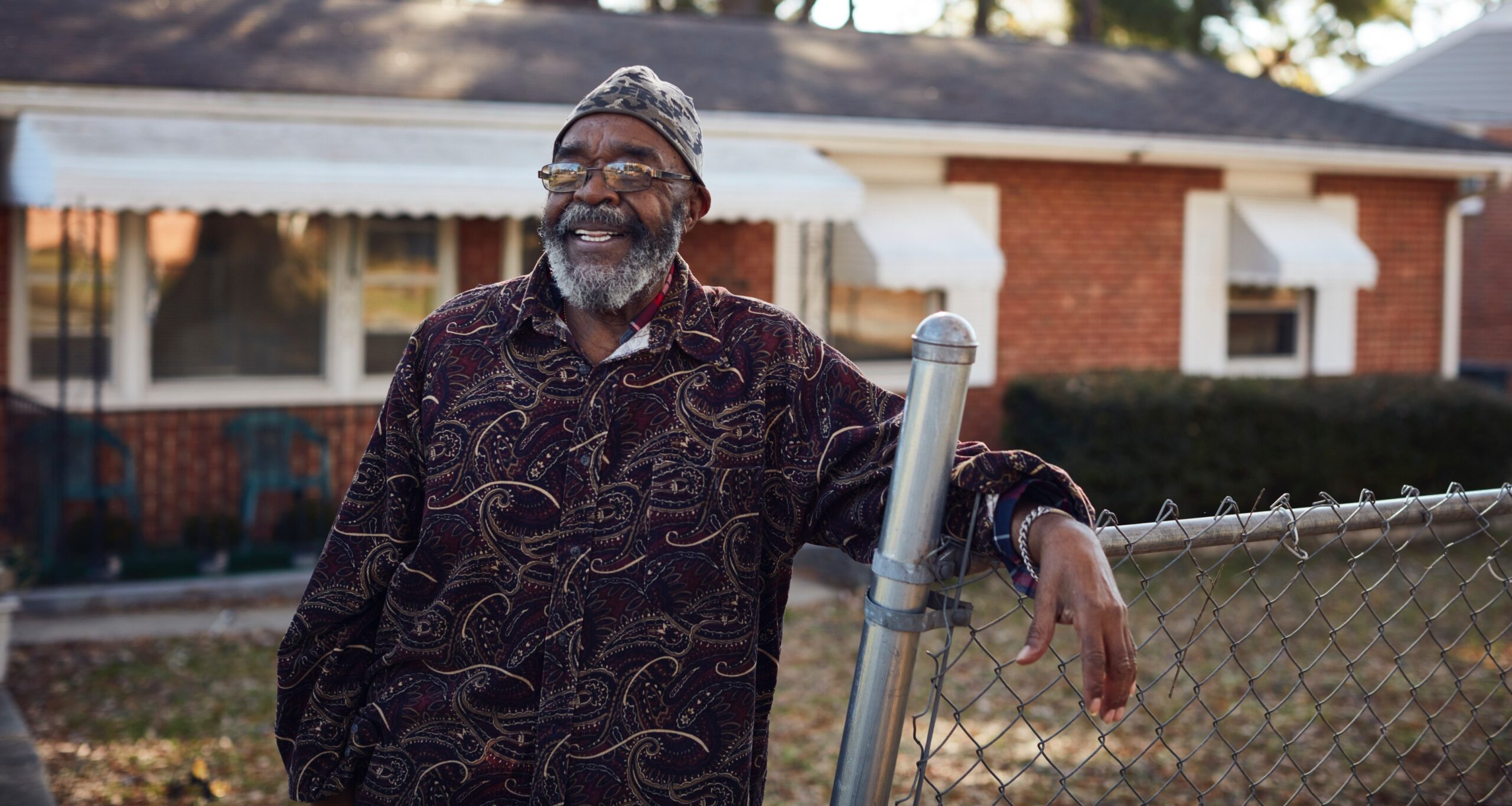 Charles smiles while leaning against the fence in front of his brick home