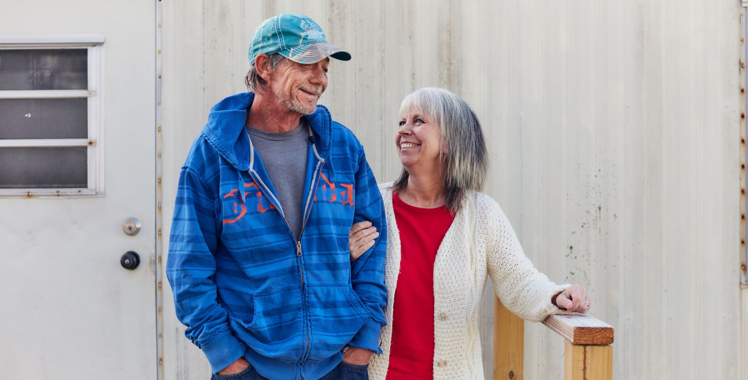 Kathy and brother David link arms and smile at each other outside David's mobile home