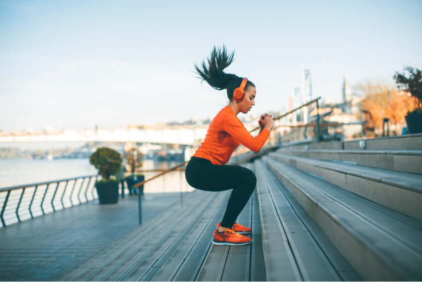 Woman exercises outdoors by jumping up steps
