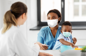 Woman in mask holds her toddler on her lap at the doctor's office