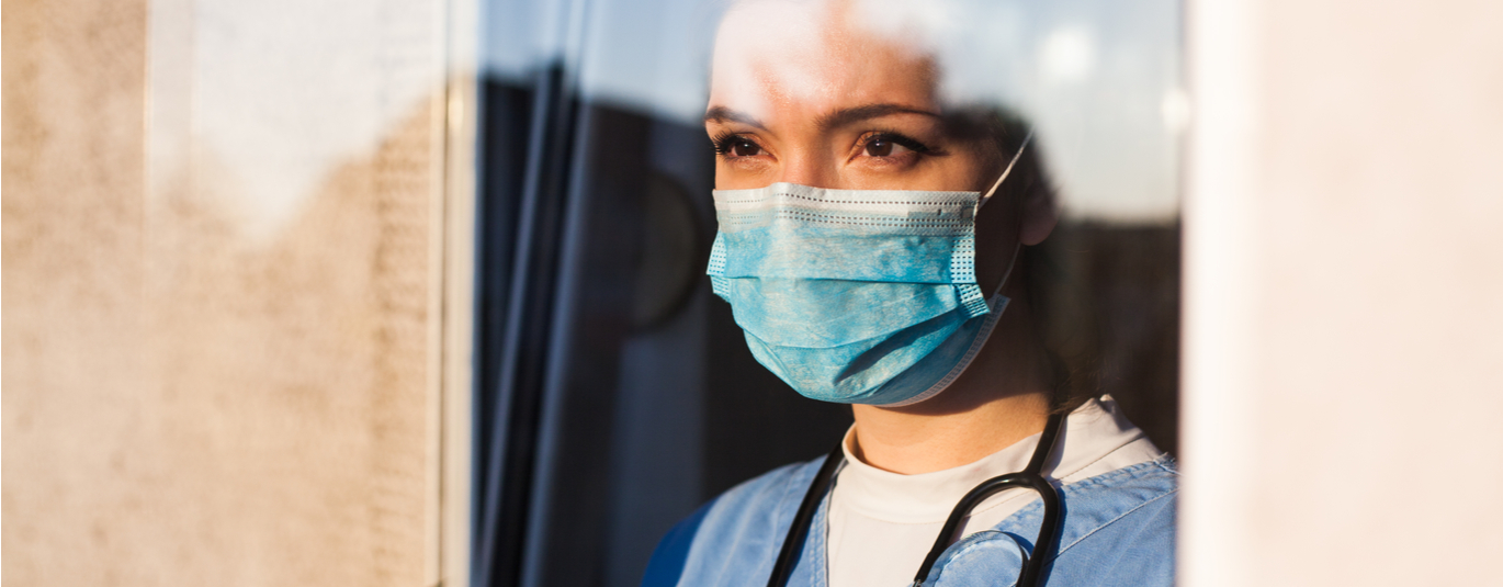 Female healthcare worker in scrubs a nd masks looks out the window with a determined expression