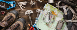 Hiking gear: shoes, a map, cell phone, and other miscellaneous equipment photographed from above