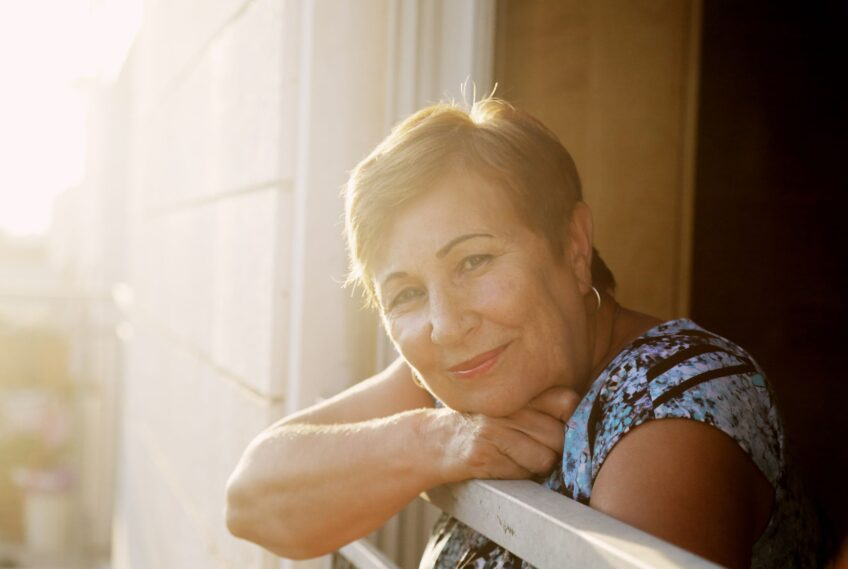 Woman leans over apartment balcony and smiles