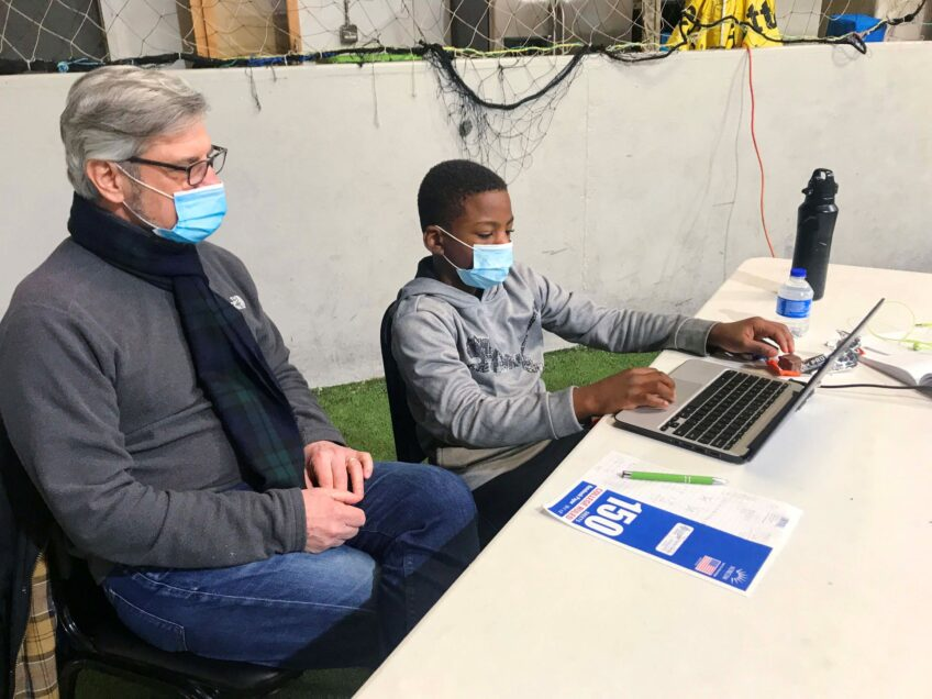 Mike Restaino and fourth-grader Zaquan, both wearing masks, sit next to each other at Zaquan's laptop