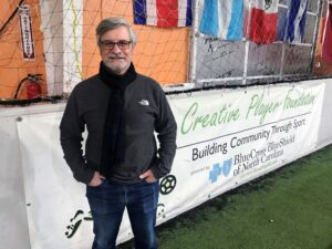 Mike Restaino posing in front of Creative Players Foundation sign