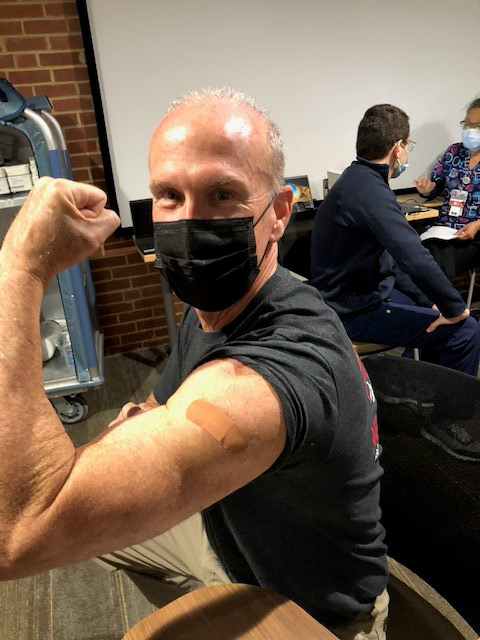 Michael Minogue shows off the bandaid on his arm from his vaccine