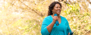 Woman power walking outside with hand weights