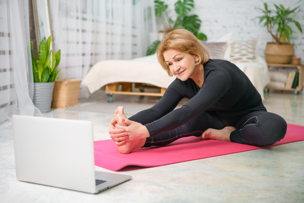 Fitness training online, senior woman at home with laptop stretches on yoga mat.