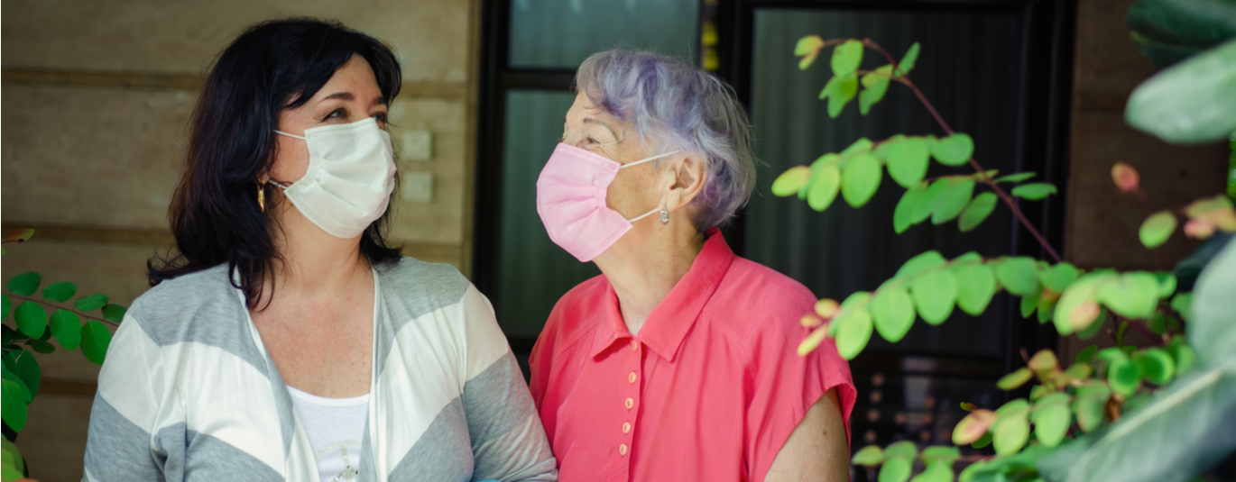 Woman walks outdoors with older relative, both wearing masks and smiling at each other