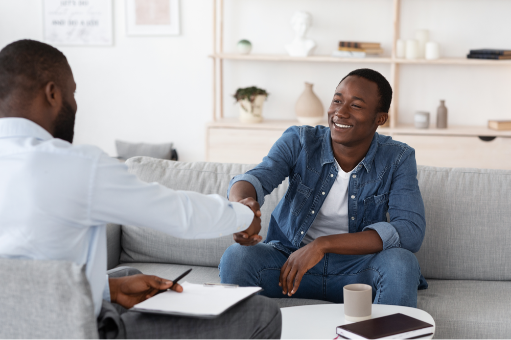 African American man and therapist shake hands, smiling
