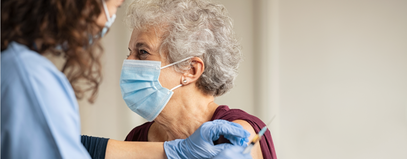 Senior woman in mask gets covid-19 vaccine