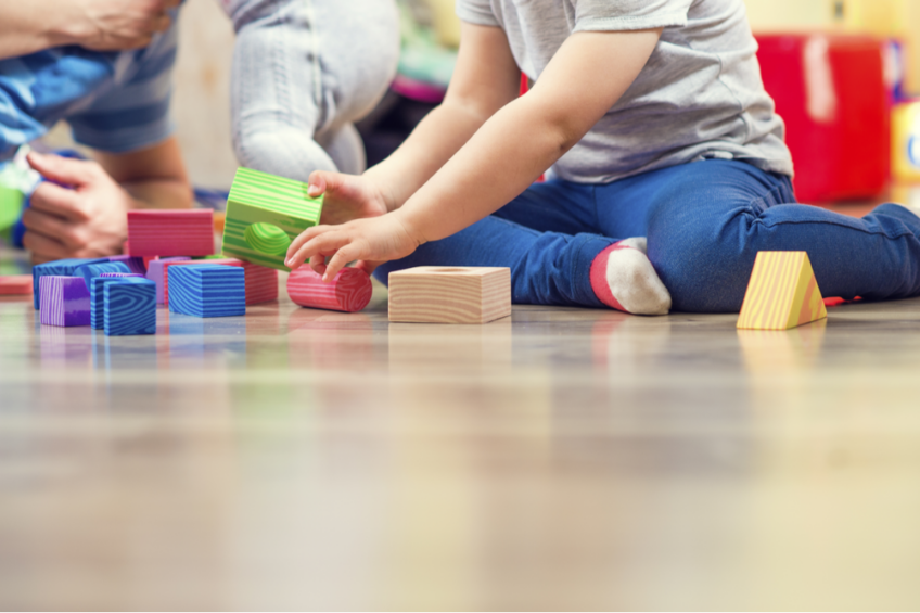 Child plays with blocks on the floor