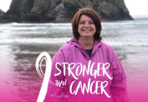 """Laura smiling in front of the ocean. Text overlay shows a cancer ribbon with the words """"stronger than cancer."""""""