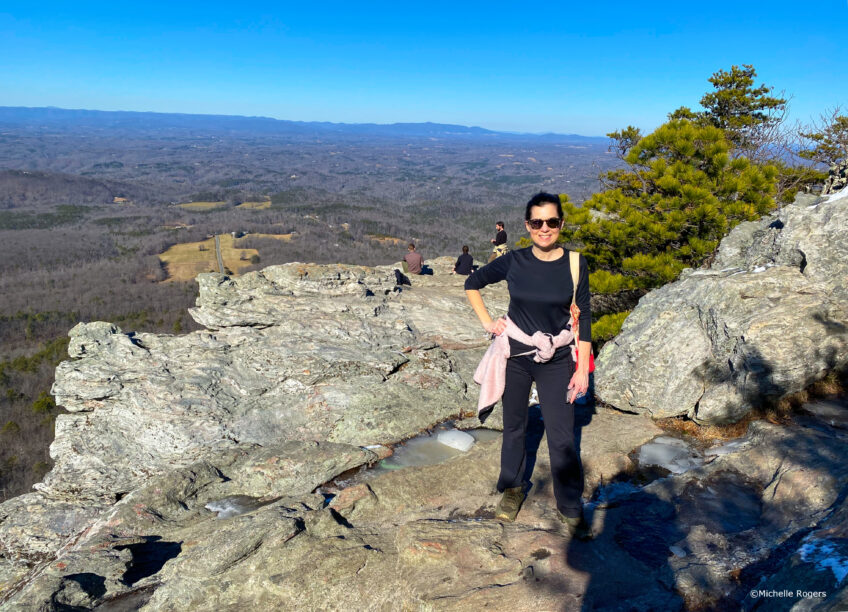 Michelle stands on a rock at the top of a mountain, with the horizon behind her.
