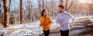 Couple runs outdoors on a trail with light snow on the grass