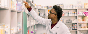 Black male pharmacist in white coat reaches for a medication on top shelf at pharmacy